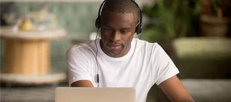 student on laptop with headphones