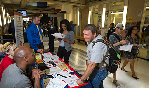 student stopping by a info table
